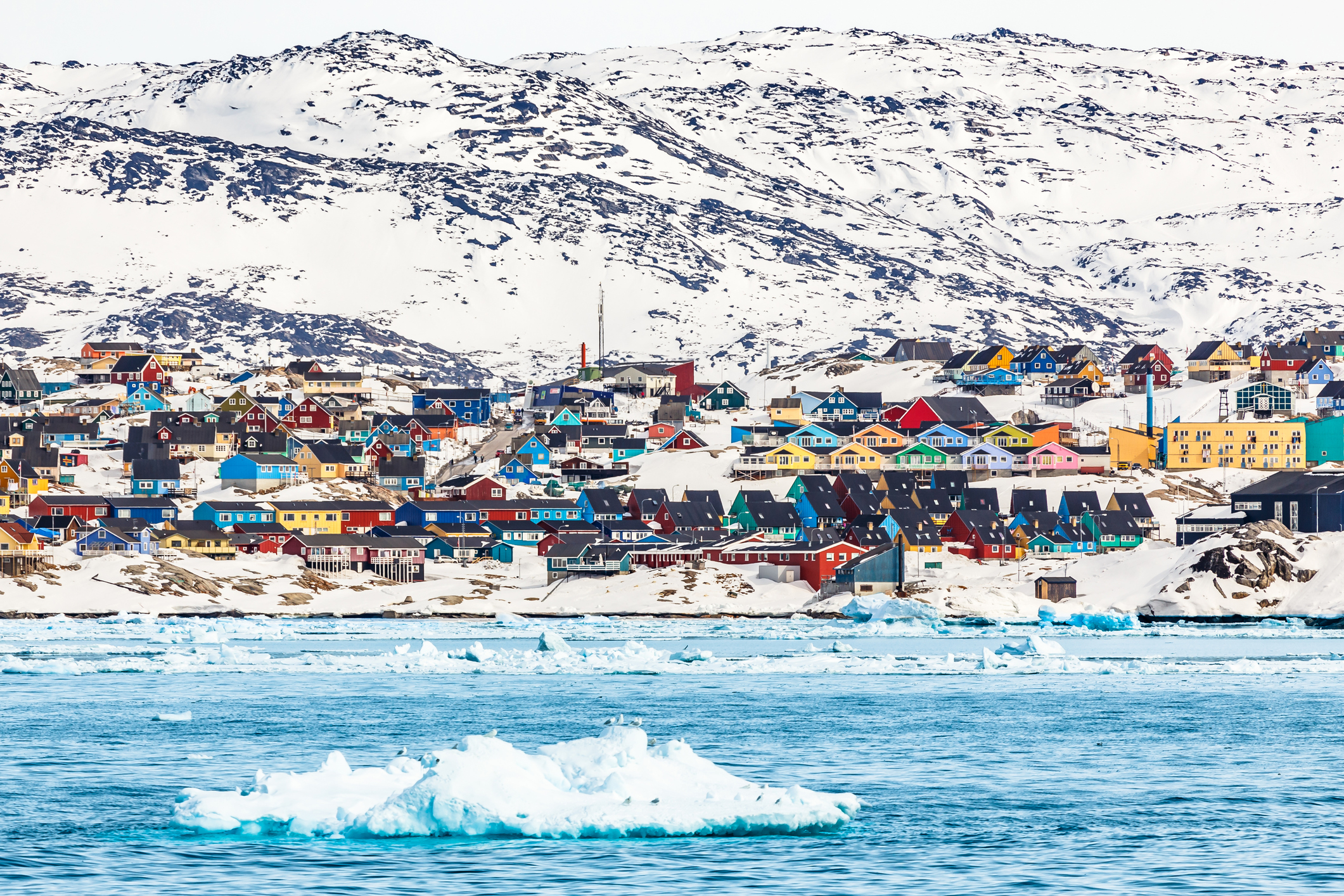 Arctic snow city panorama with colorful Inuit houses on the rocky hills covered in snow with icebergs in the foreground, Ilulissat, Greenland